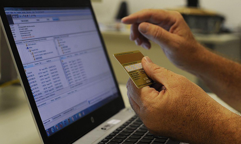 um notebook e duas mãos com um cartão bancário sobre o teclado do computador