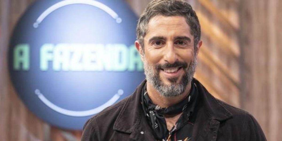 Marcos Mion posado sorrindo olhando para frente com letreiro de A Fazenda atrás