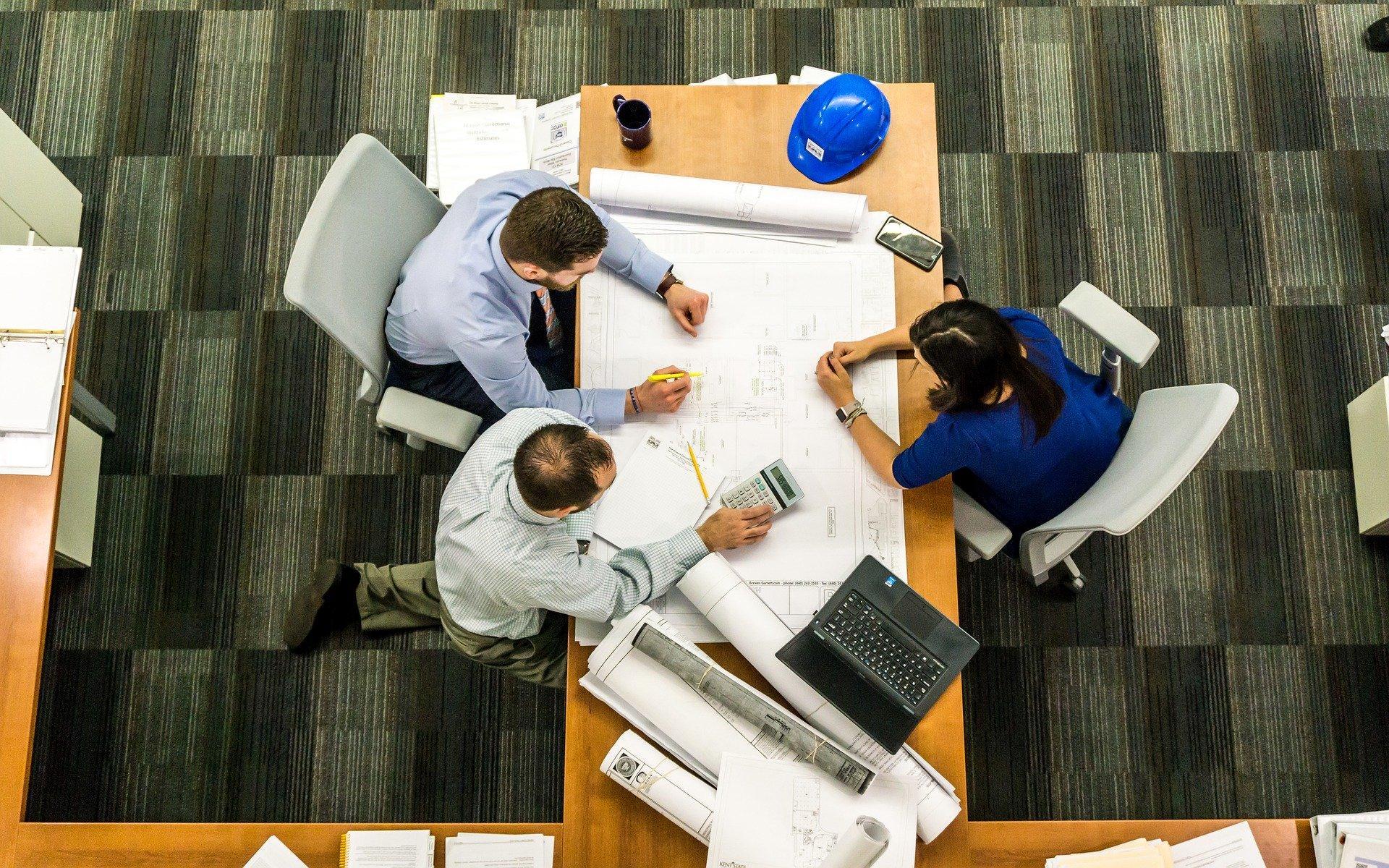 Três pessoas em reunião em volta de uma mesa. Crédito Pronampe.
