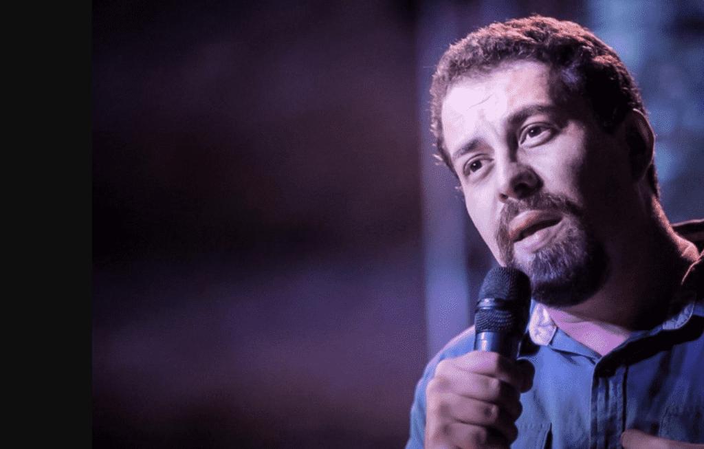 Foto mostra Guilherme Boulos falando ao microfone.