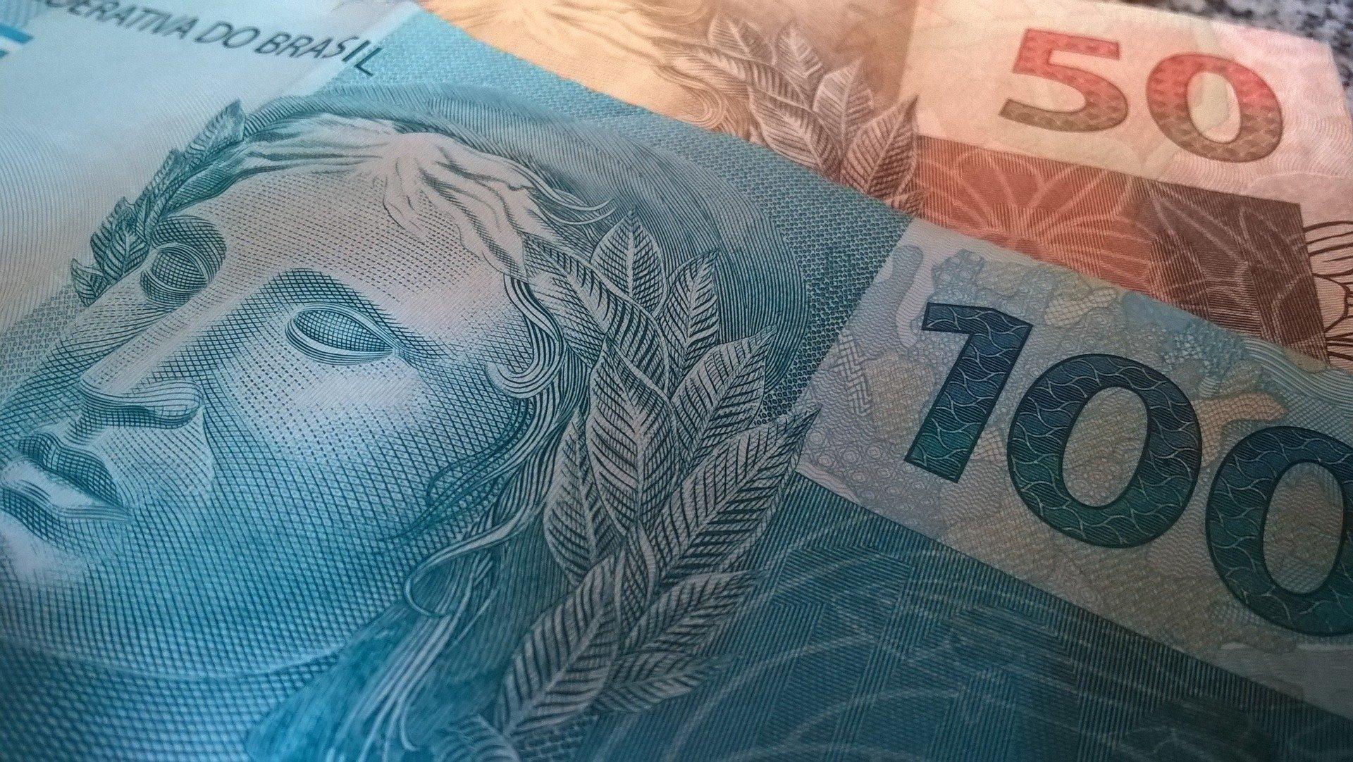 cédula de 100 reais sobre outra cédula de 50 reais