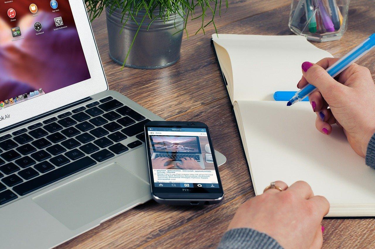 Como criar um bom portfólio online? Imagem mostra mulher anotando em caderno ao lato de celular e notebook