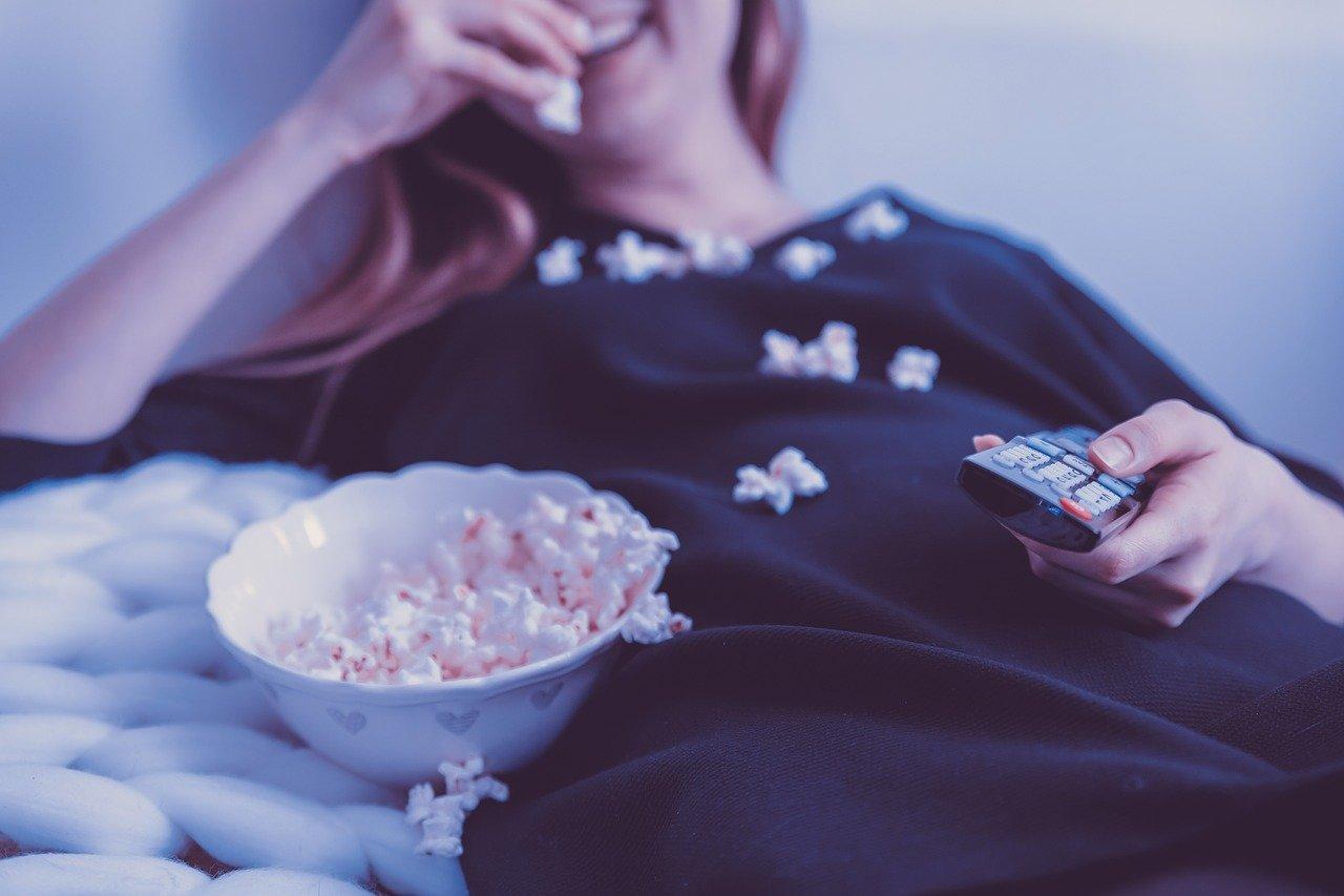 Mulher comendo pipoca e assistindo uma série premiada pela Prime Video