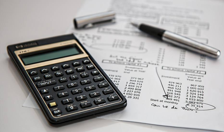 calculadora, contas e canetas.