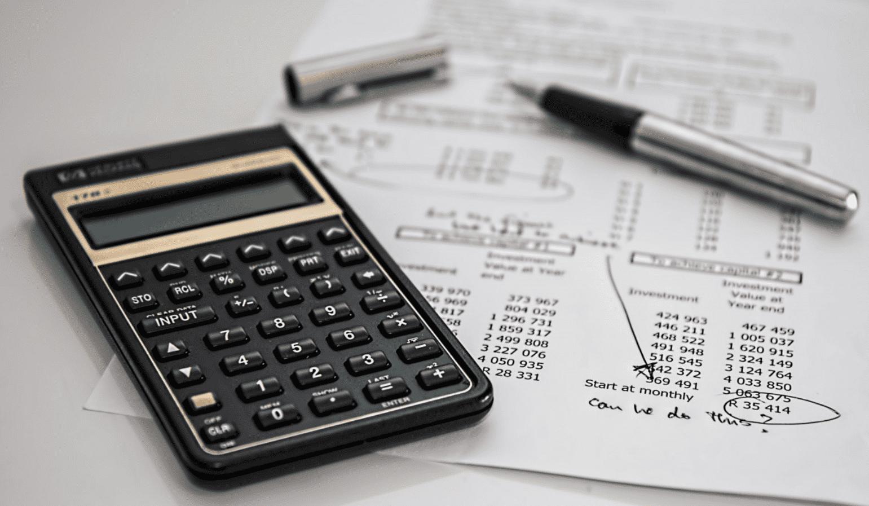 Foto mostra uma calculara, caneta e folhas em cima de uma mesa.
