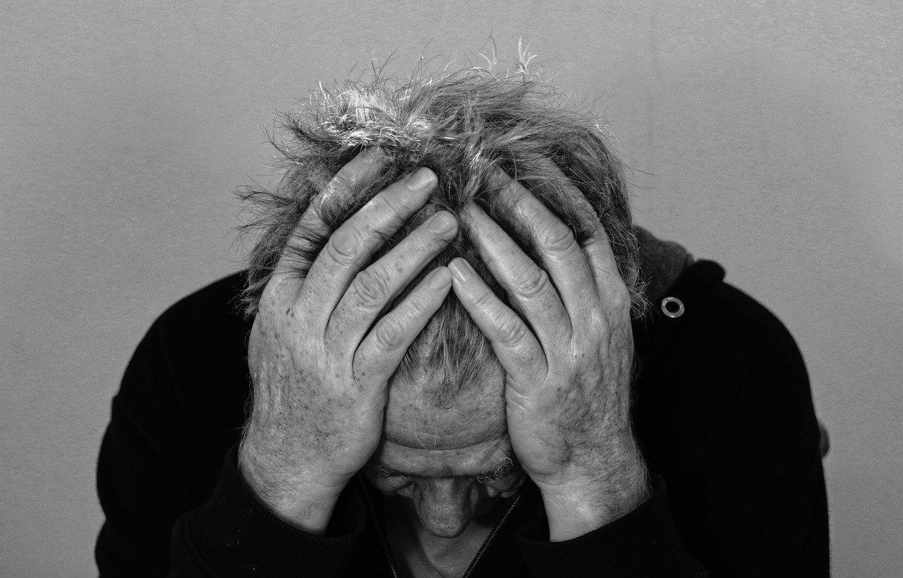 homem de cabeça baixa com as duas mãos sobre a cabeça. imagem em preto e branco