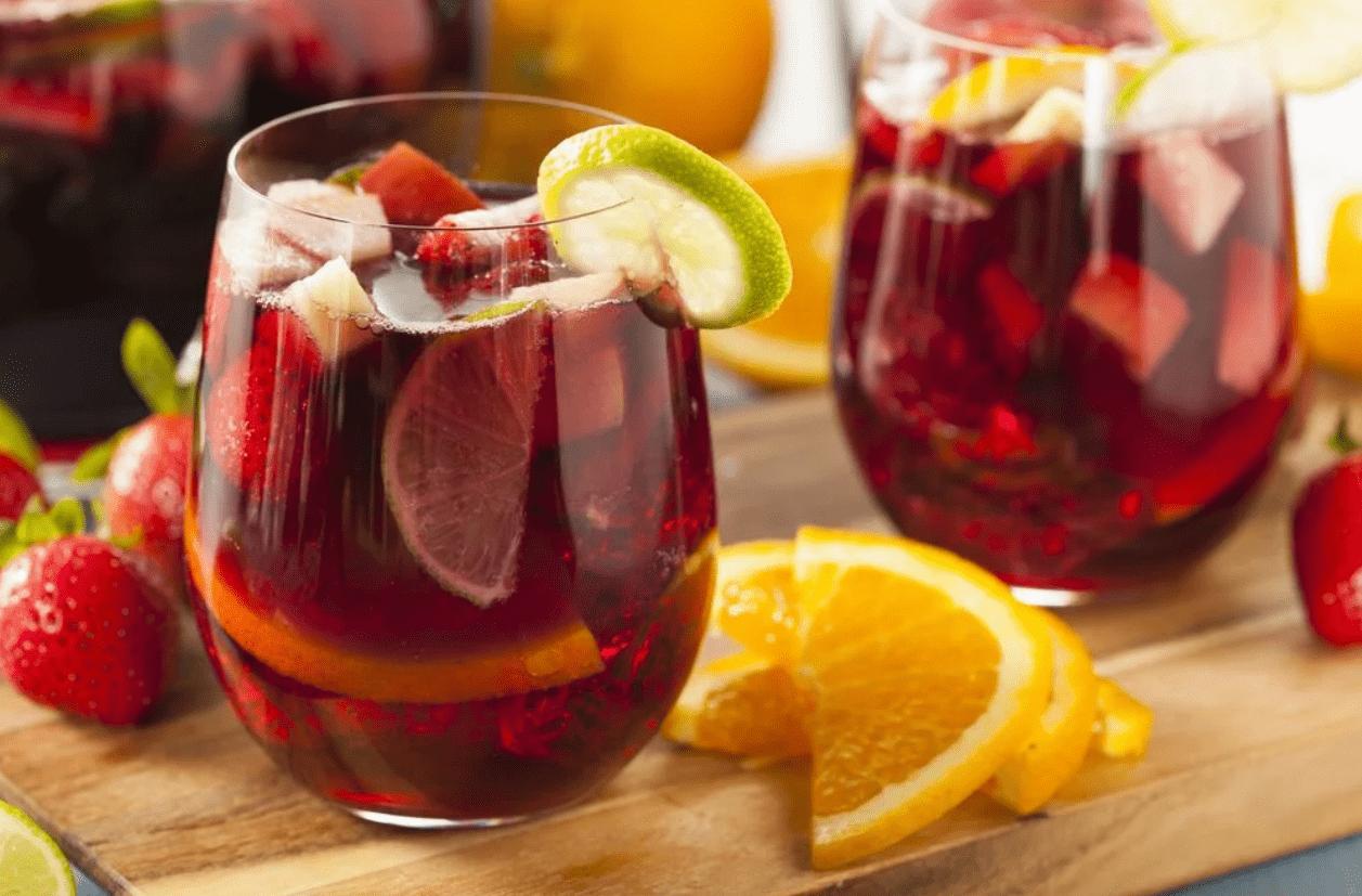 Foto mostra dois copos com sangria em cima de uma tábua. Ao lado de frutas picadas.