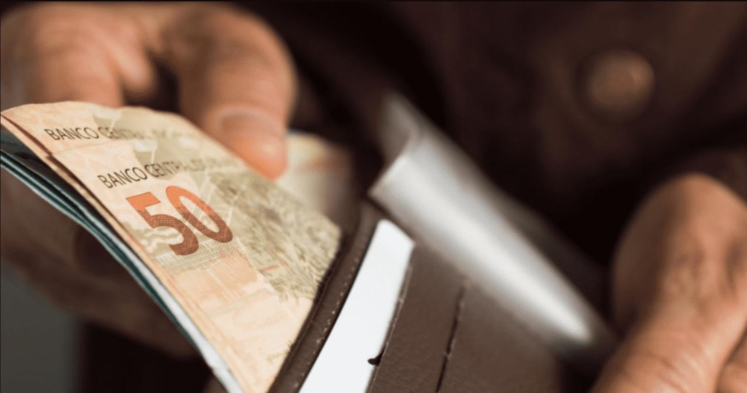 Imagem mostra mão colocando notas de 50 reais em uma carteira.