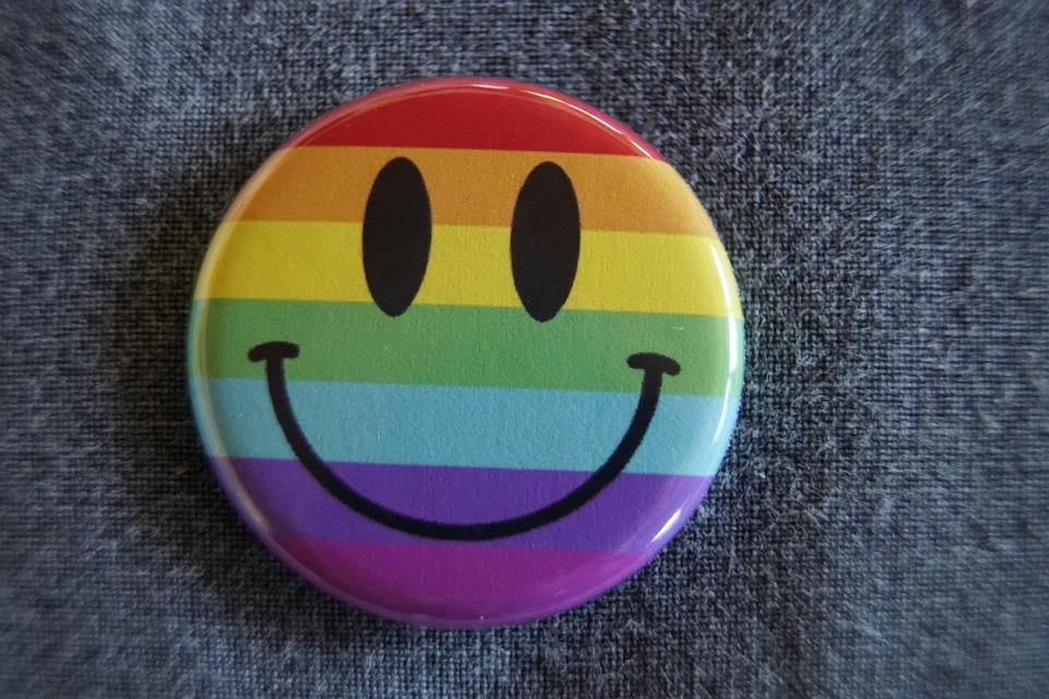 Botão com emoji de sorriso com as cores da bandeira lgbtqi+