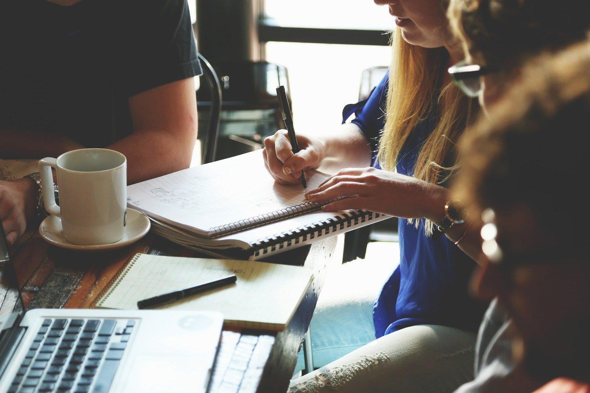 Pessoas em reunião. Mesa com papeis, notebook e copos.
