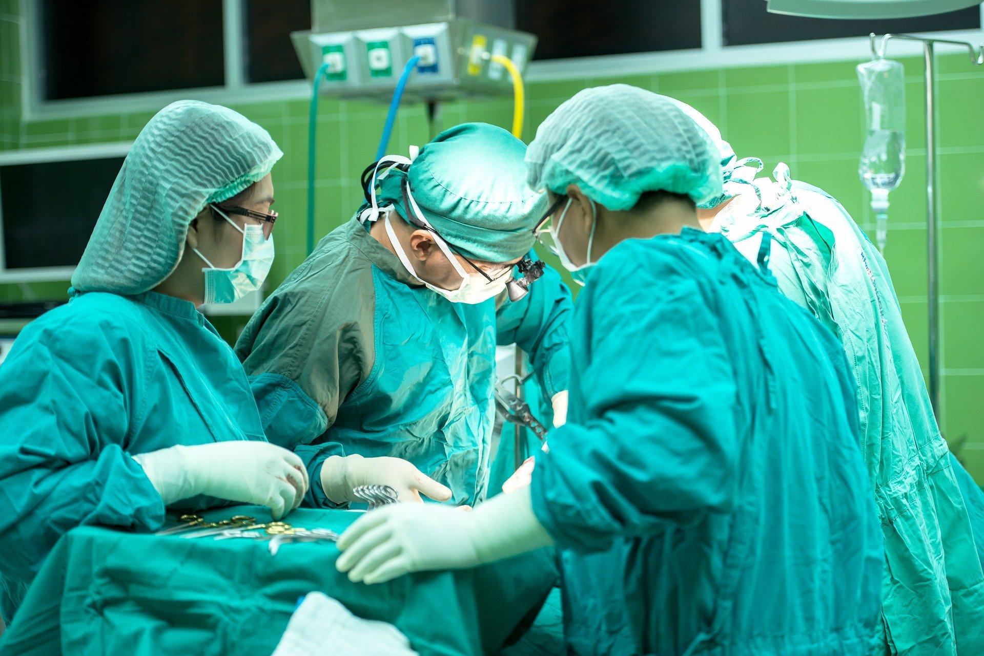 Três médicos com roupa azul com instrumentos médico operando um indivíduo