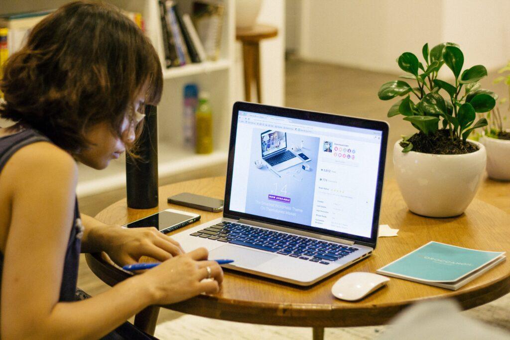 Mulher fazendo anotações com o notebook a frente