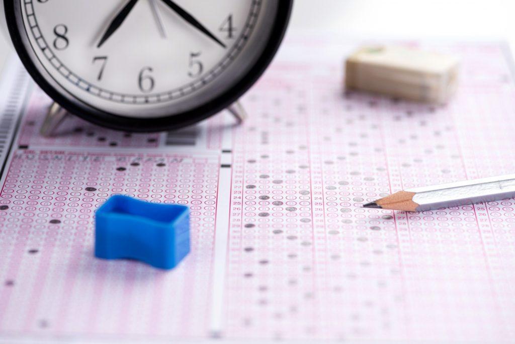 folha de respostas com relógio de mesa, apontador sem reserva azul e lápis grafite