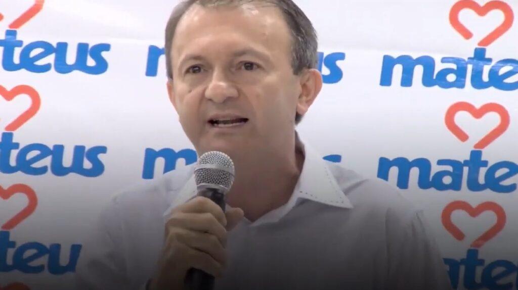 Ilson Mateus com microfone em uma das mãos e na frente de um painel com o logotipo do Grupo Mateus