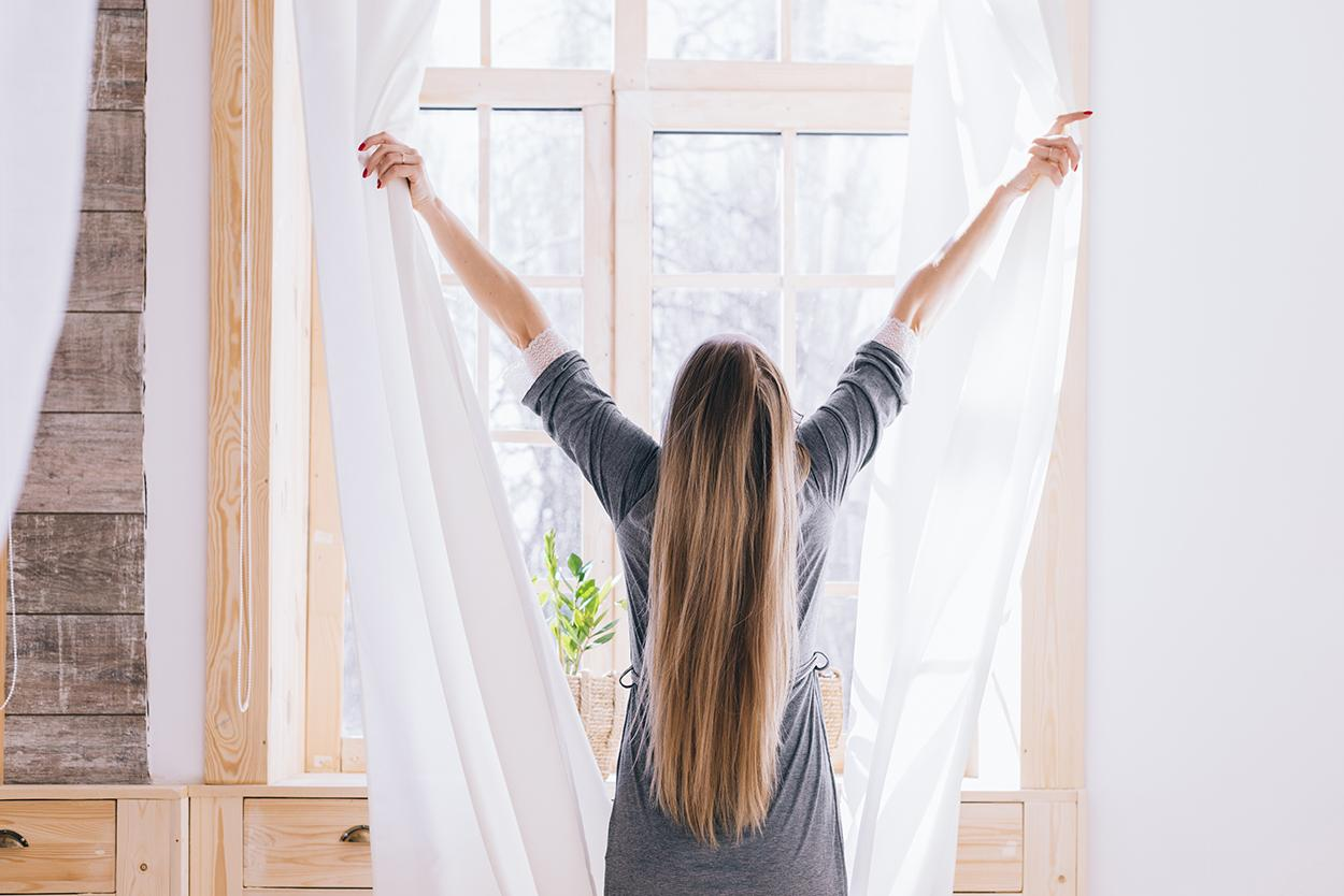 Como refrescar o quarto: Imagem de mulher abrindo cortinas