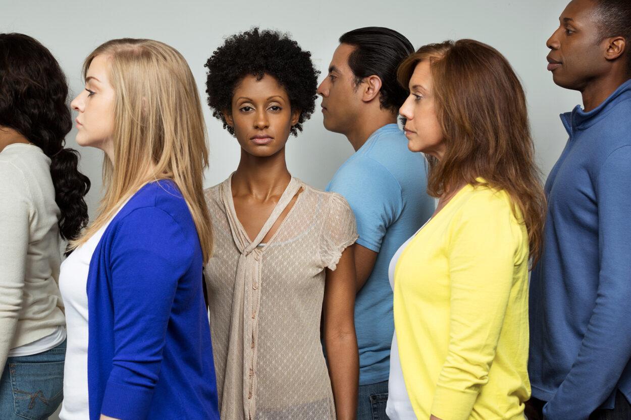 mulher negra de frente enquanto brancos e homens estão de perfil