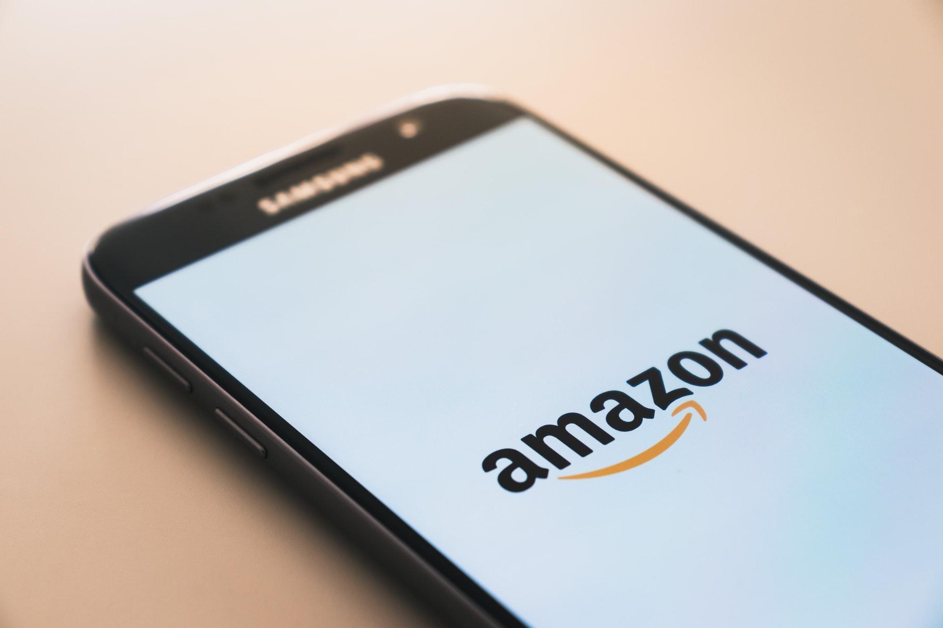 Como investir na Amazon. Celular mostrando logo da Amazon.