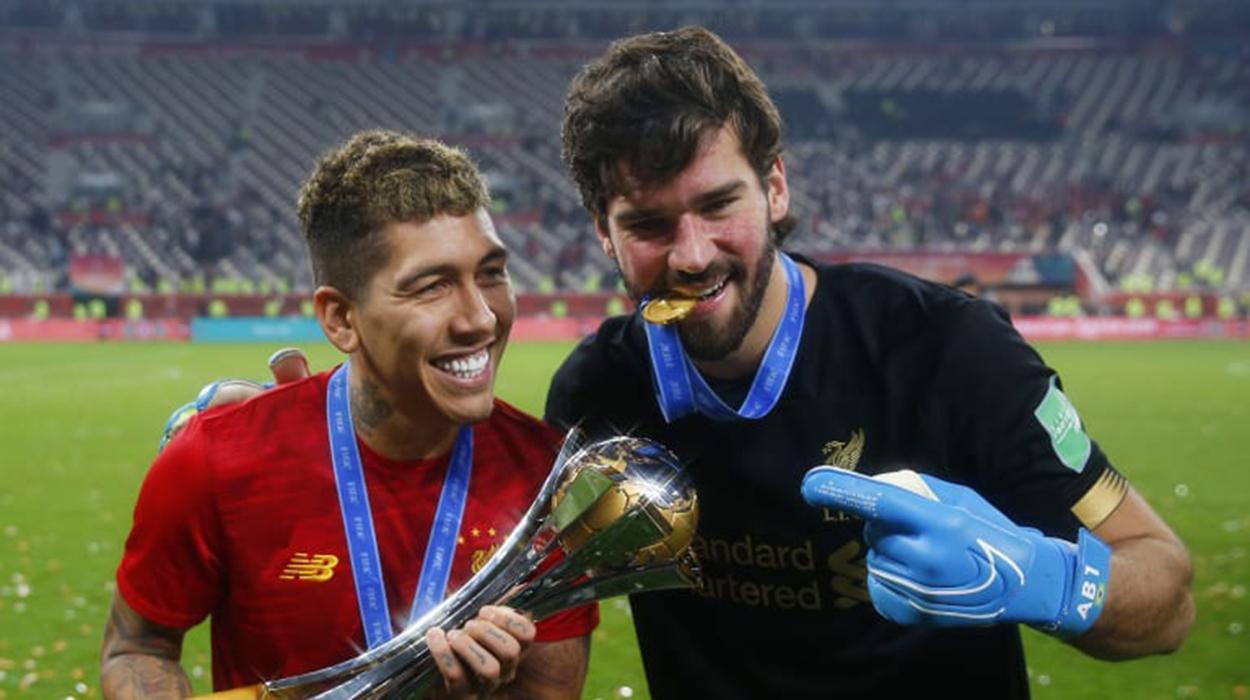 Firmino e Alisson seguram o troféu do Mundial de Clubes conquistado pelo Liverpool; edição de 2020 está incerta
