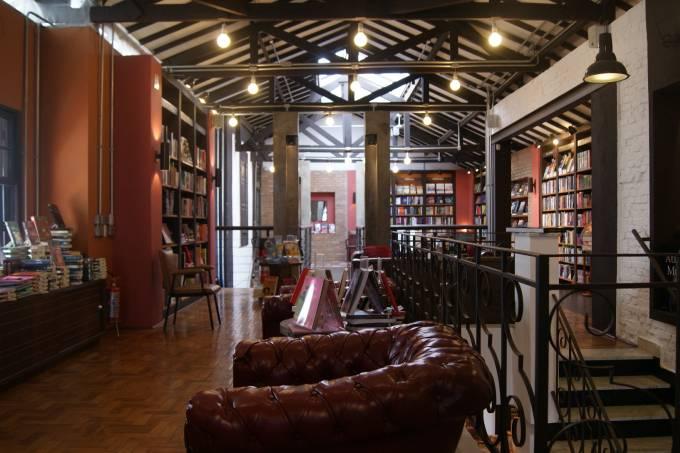 interior de livraria calma com prateleiras de livros ao fundo e poltrona confortável à frente