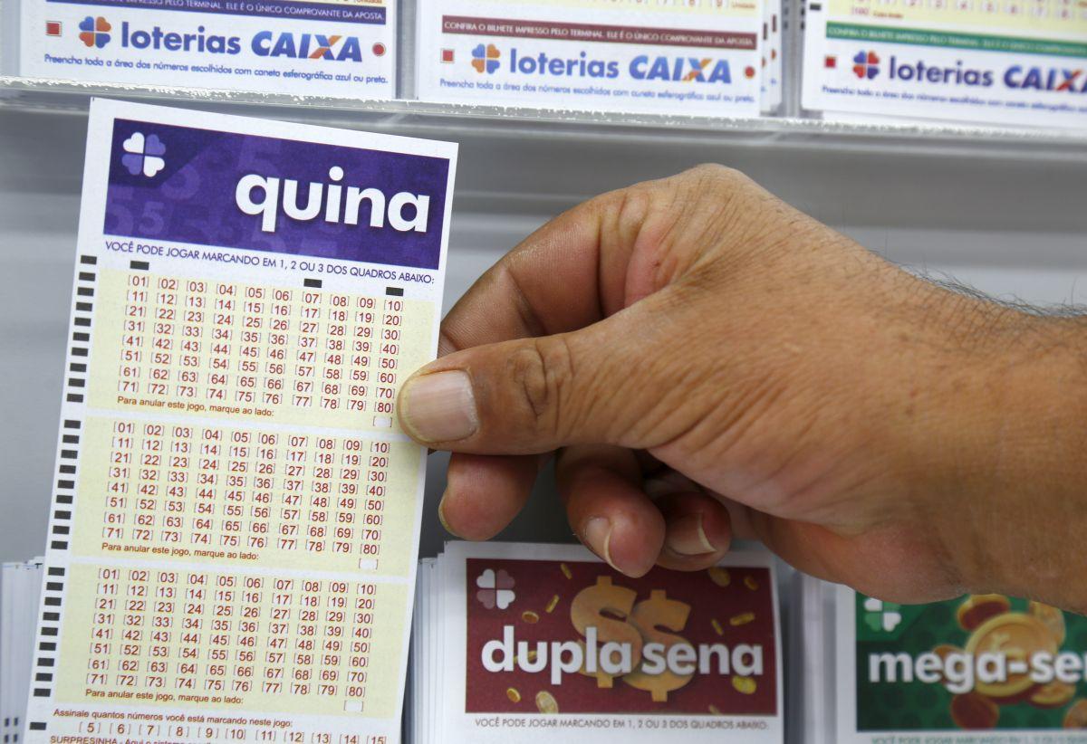 resultado da Quina de ontem - a imagem mostra uma mão pegando o volante da Quina que está dentro de uma caixinha transparente