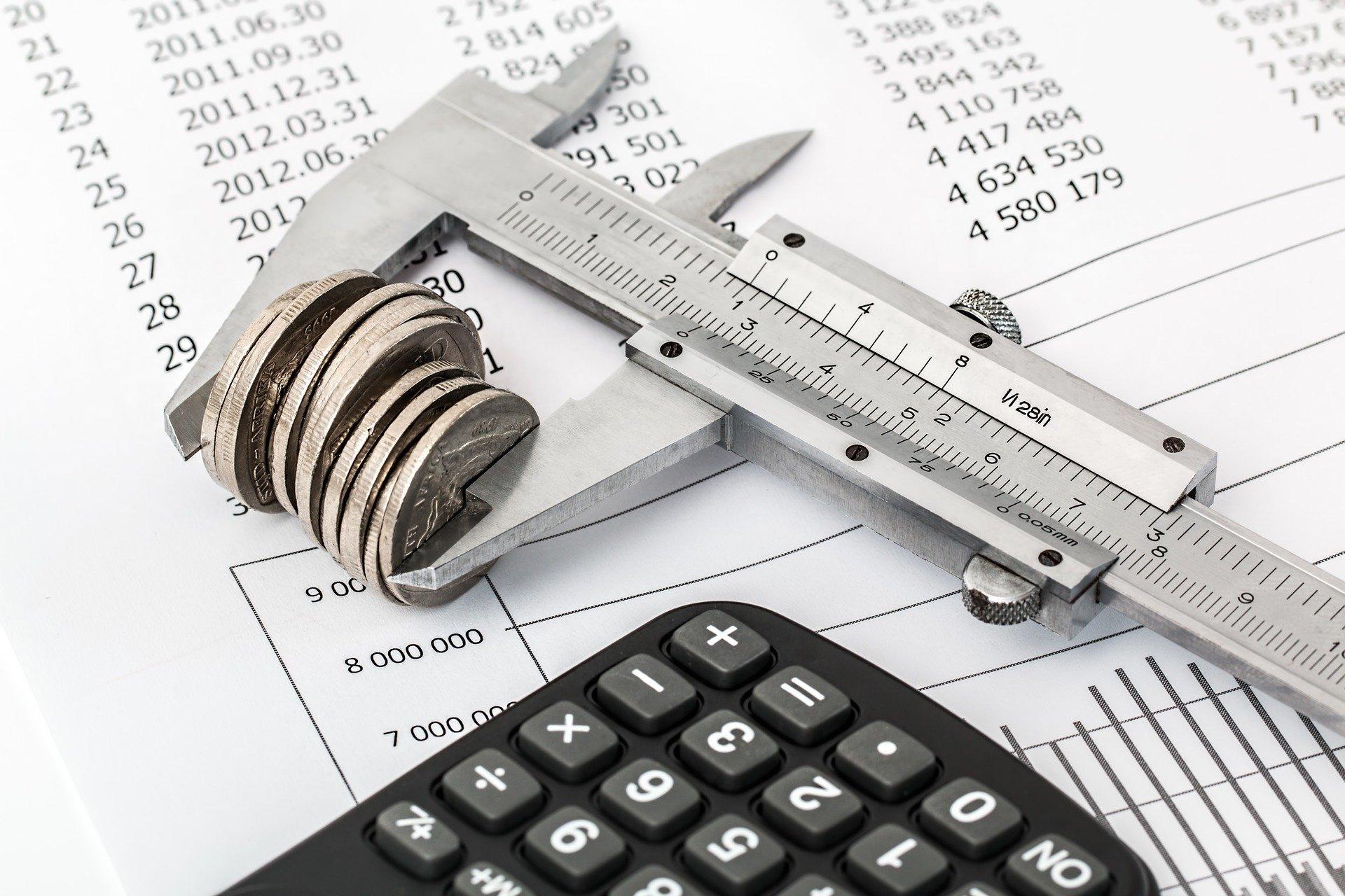 moedas empilhadas e encaixadas em medidor com calculadora ao lado e sobre papéis com números e planilhas