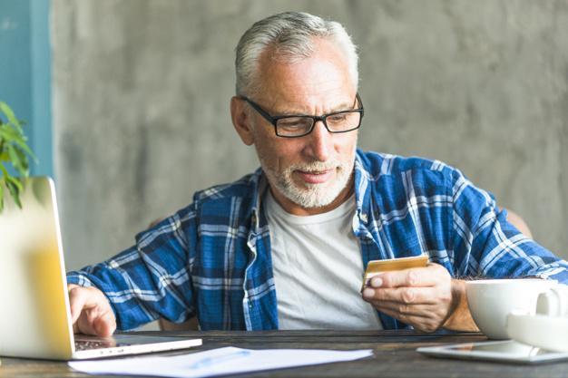 Homem usando cartão de crédito em frente ao notebook