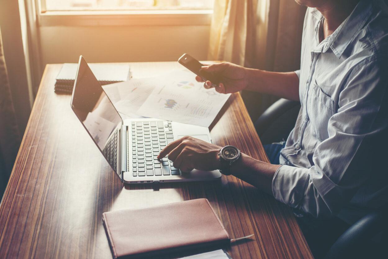 Vendas por whatsapp: homem digitando no notebook e mexendo no celular