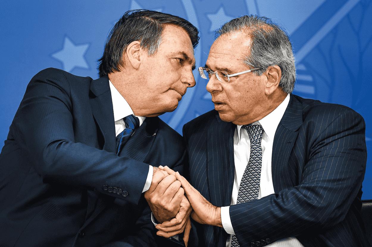 Presidente da República, Jair Bolsonaro à esquerda, e Minsitro da Economia, Paulo Guedes, à direita. Ambos estão ao lado um do outro, e com as mãos dadas
