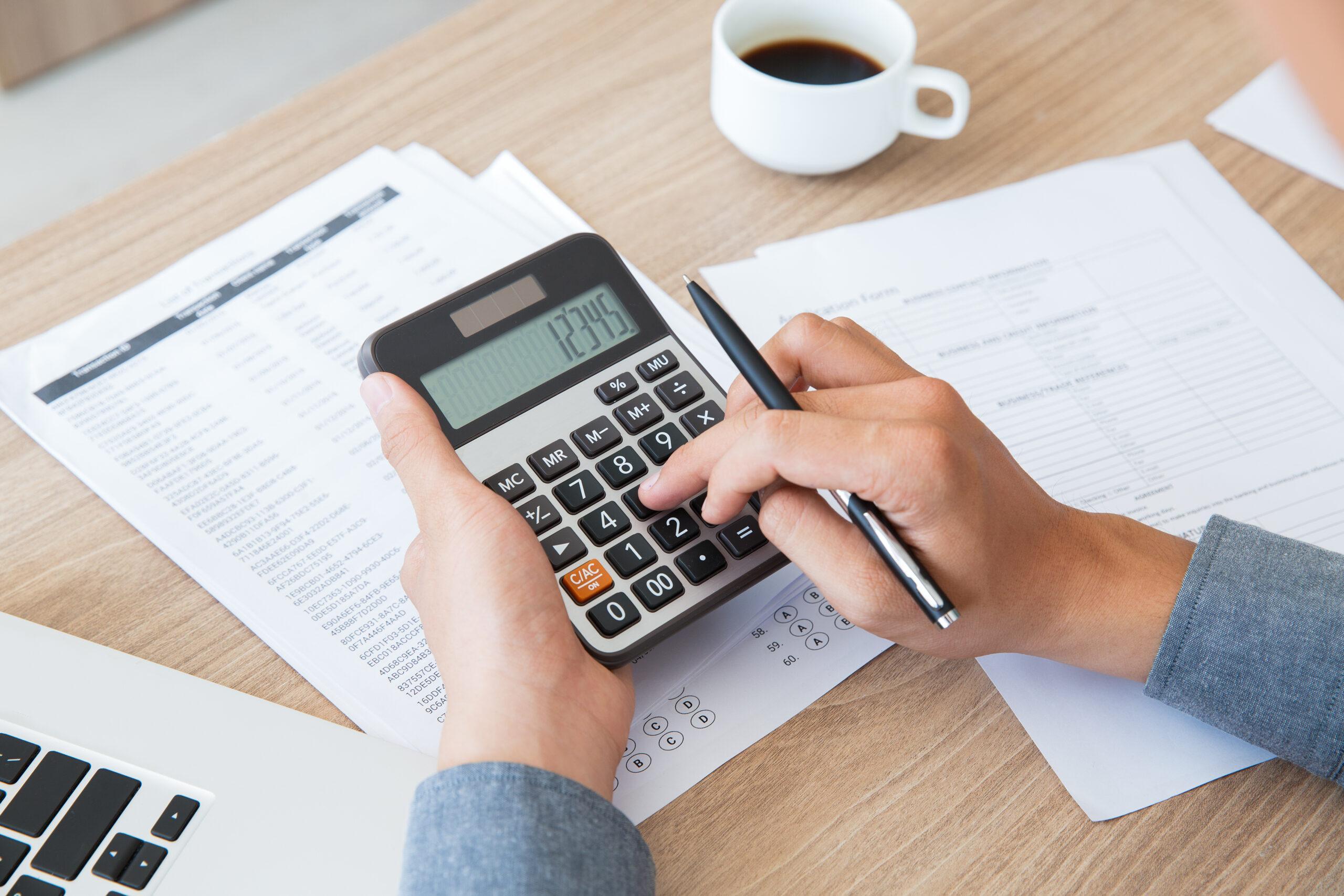 Pessoa com calculadora. Impostos federais, estaduais e municipais.