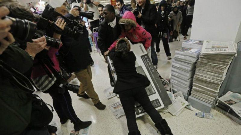 Clientes em loja disputando caixa do produto e pessoas gravando a cena.