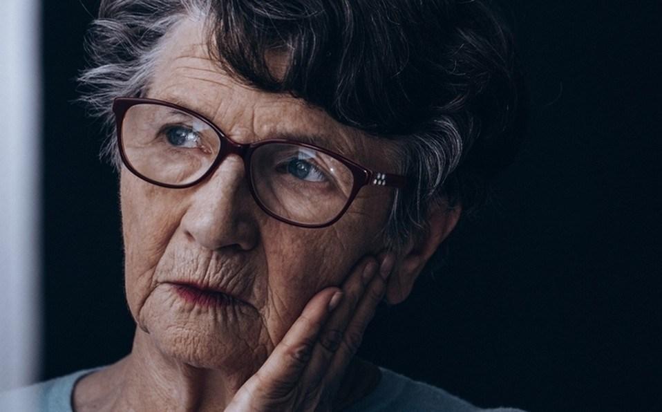 Foto mostra senhora idosa com mão no rosto