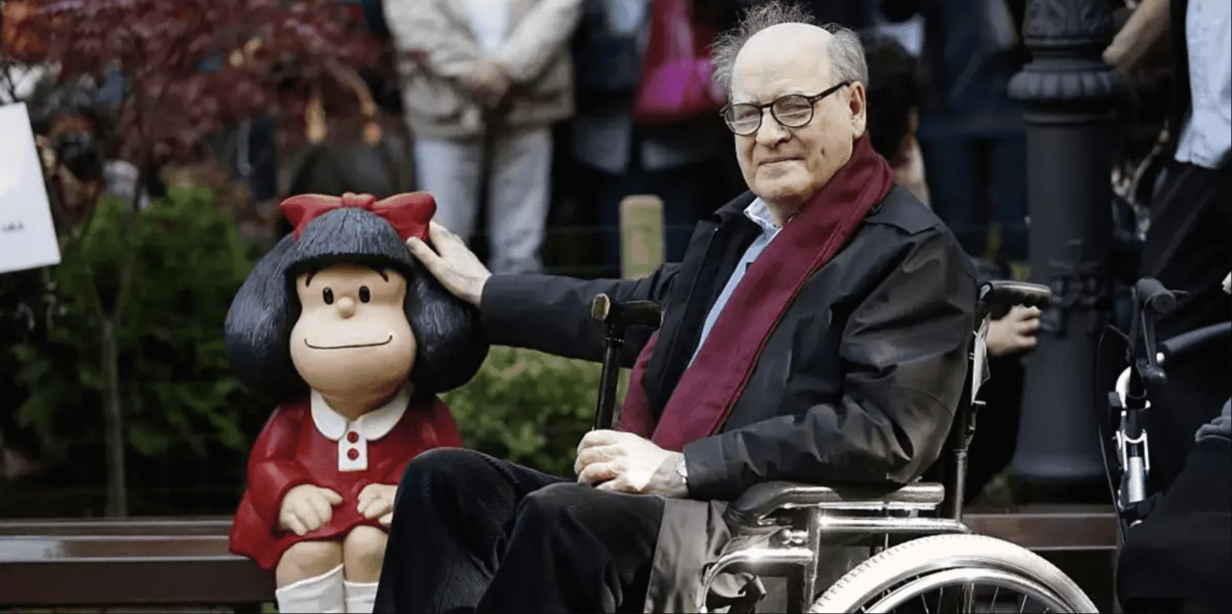 Foto mostra Quino ao lado de uma escultura da Mafalda