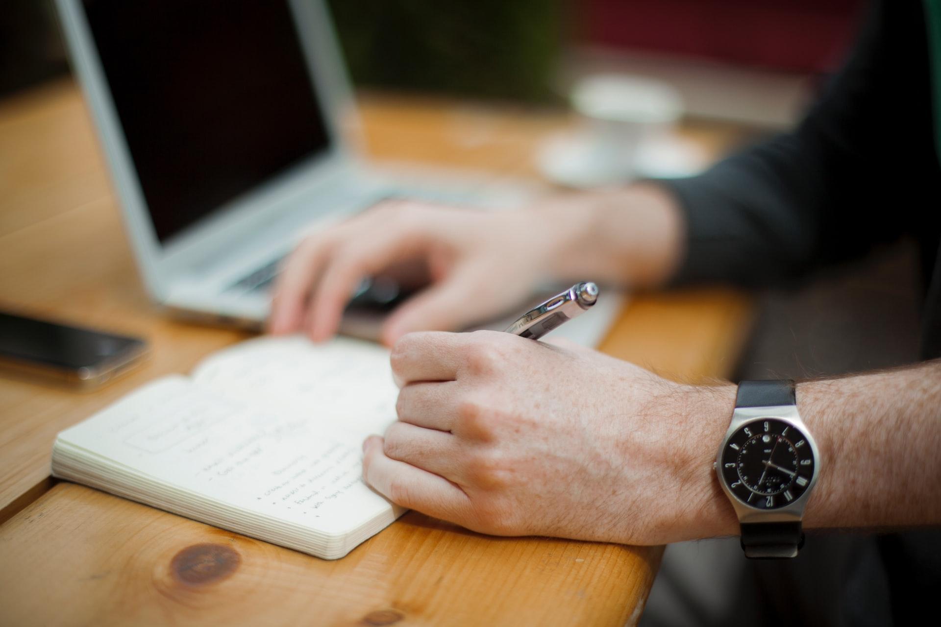 Homem escrevendo com relógio no pulso.
