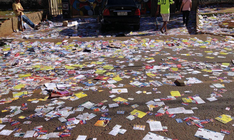 Foto mostra rua cheia de santinhos eleitorais