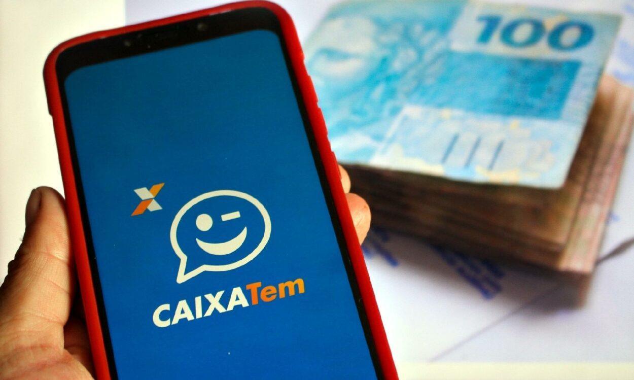 celular com logotipo do aplicativo Caixa Tem e cédulas de dinheiro ao fundo