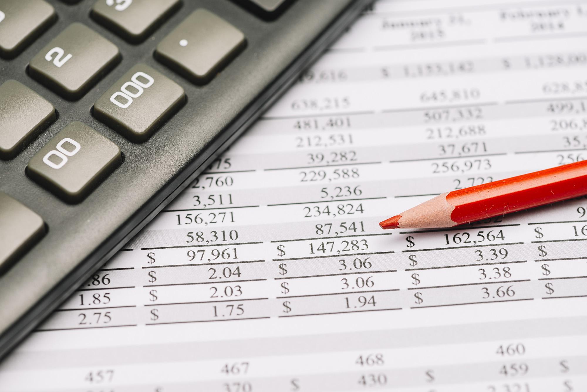 Foto mostra tabela com cálculos e calculadora.