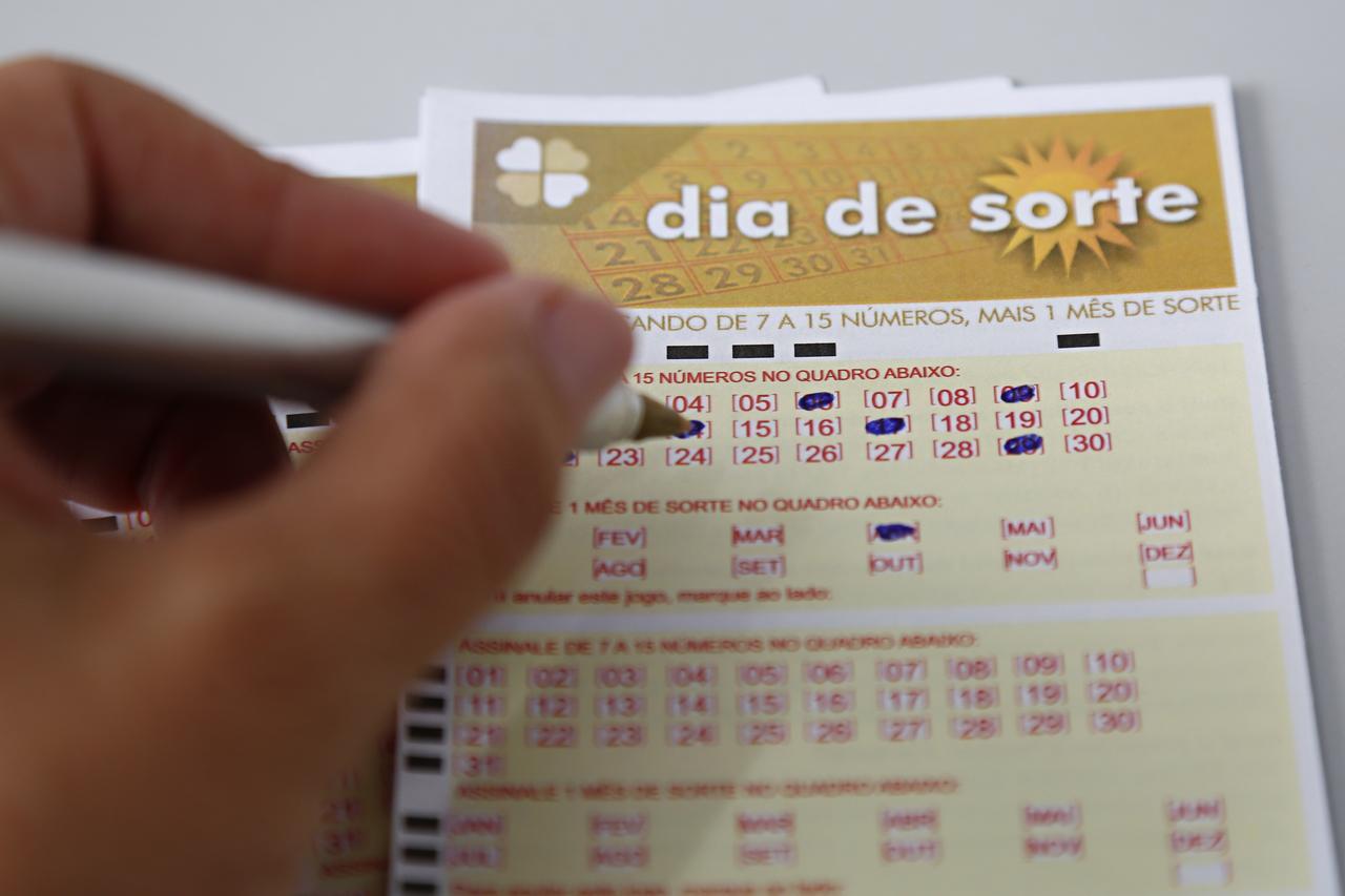 Dia de Sorte concurso 374 - A imagem mostra uma mão segurando uma caneta e marcando números no volante do Dia de Sorte