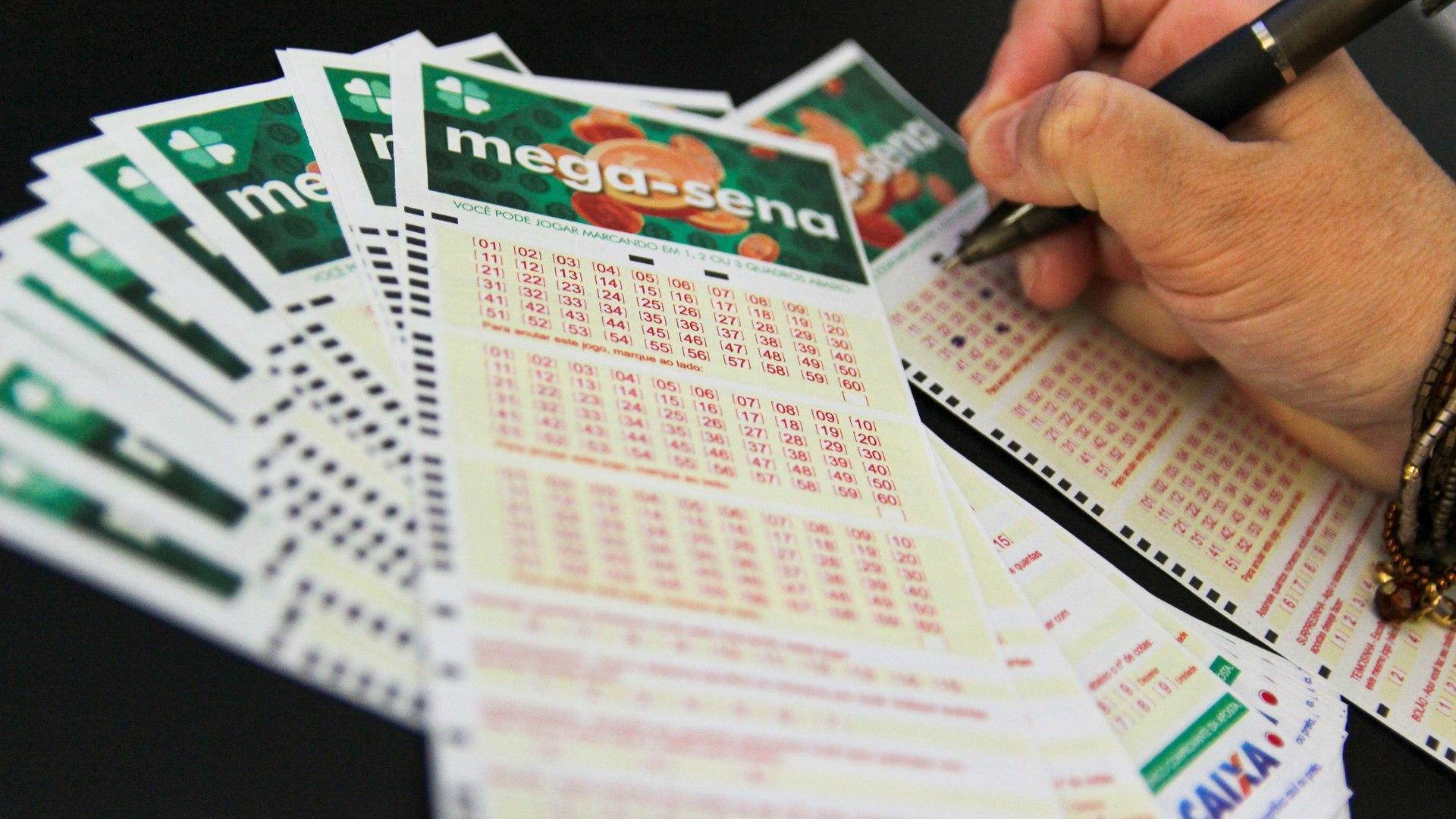 resultado da mega-sena - A imagem mostra um leque de volantes da Mega-Sena e uma mão ao lado marcando número em um volante separado