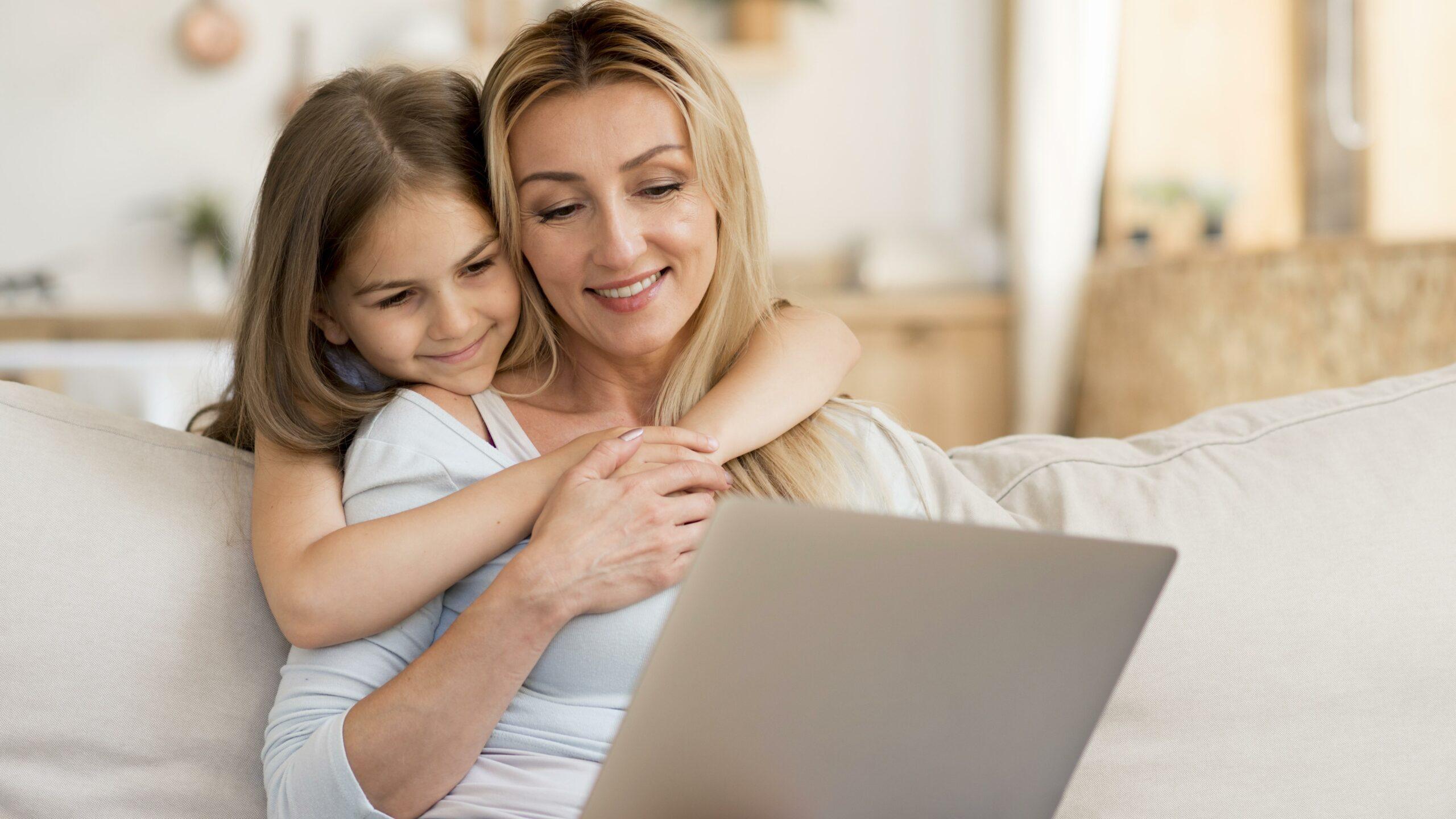 Mulher usando notebook enquanto filha a abraça. Dependentes do MEI