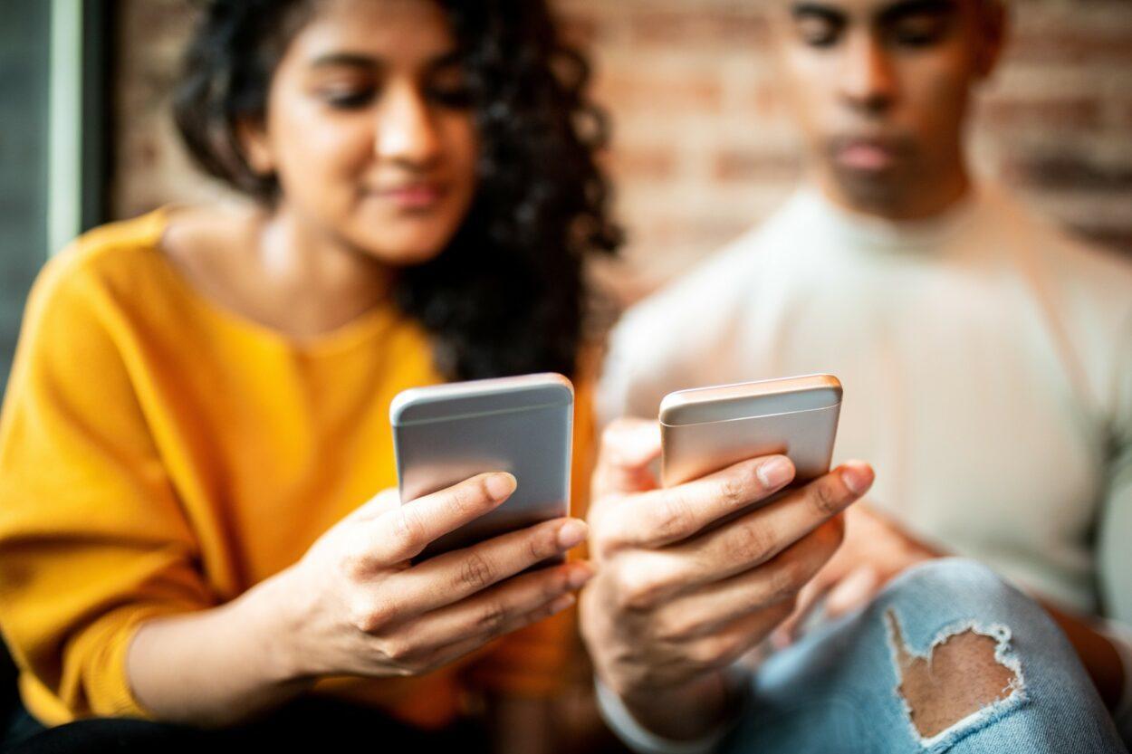 mulher e homem segurando seus respectivos celulares, um ao lado do outro