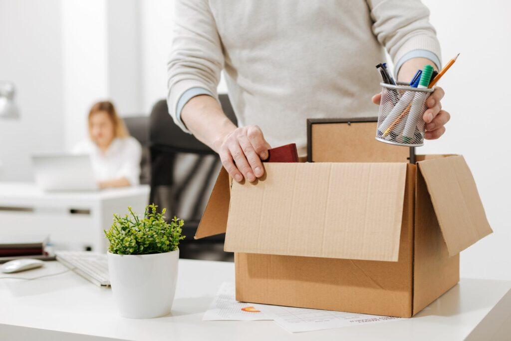 pessoa colocando pertences em caixa de papelão