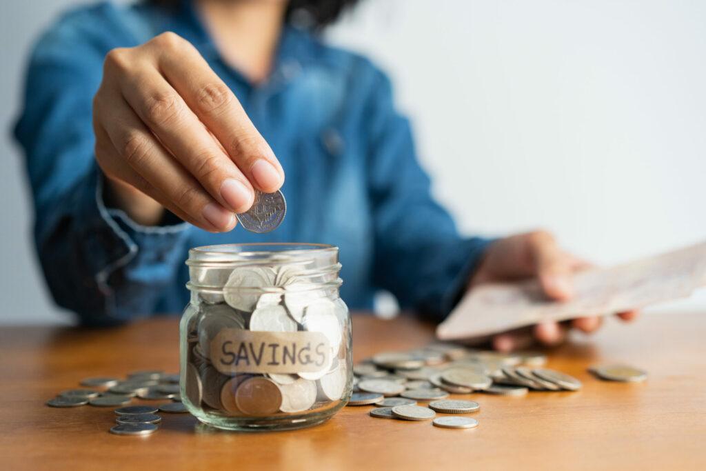 mulher de camisa azul guardando moeda em pote transparente já cheio