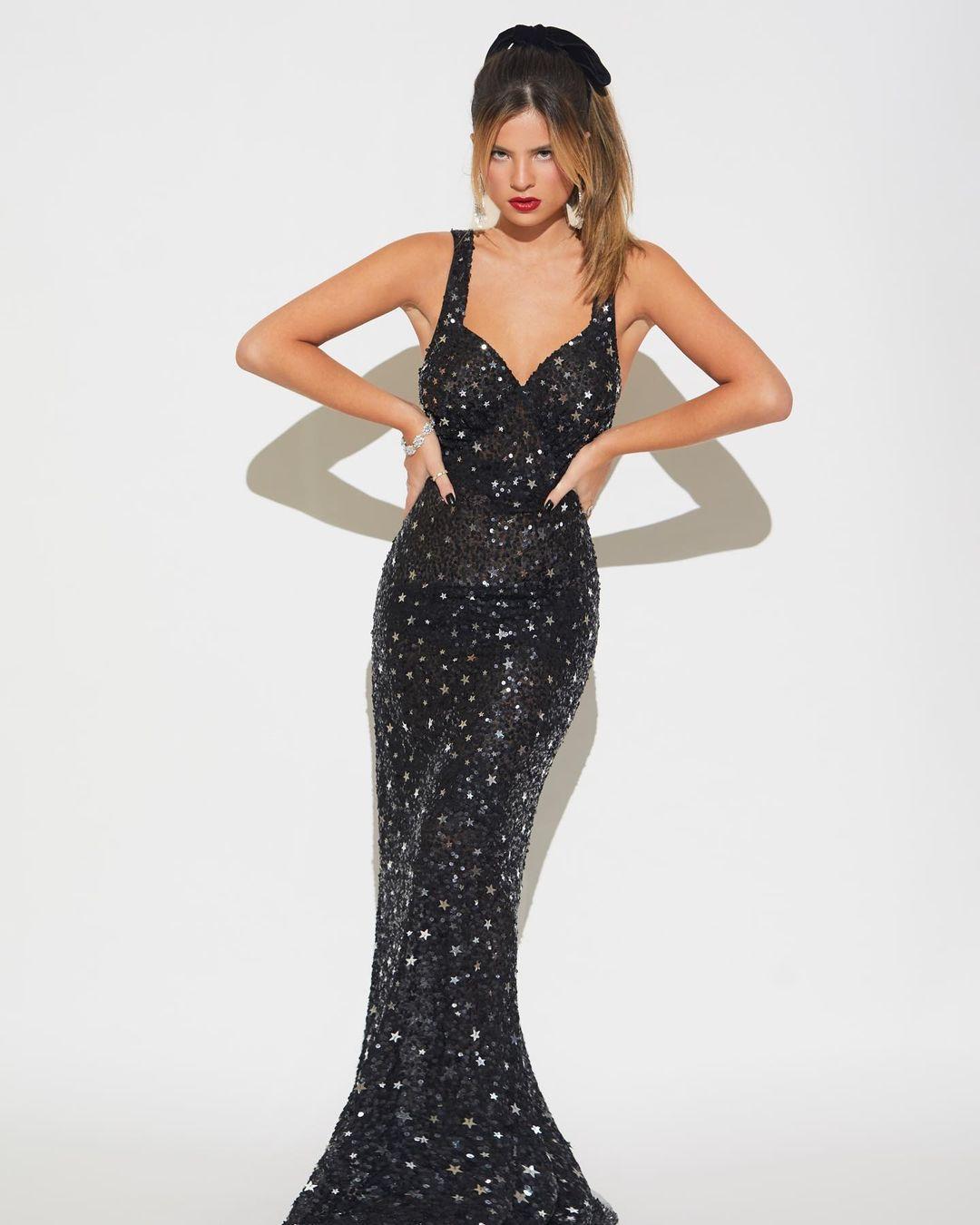 Imagem mostra cantora Giulia Be com vestido longo brilhante