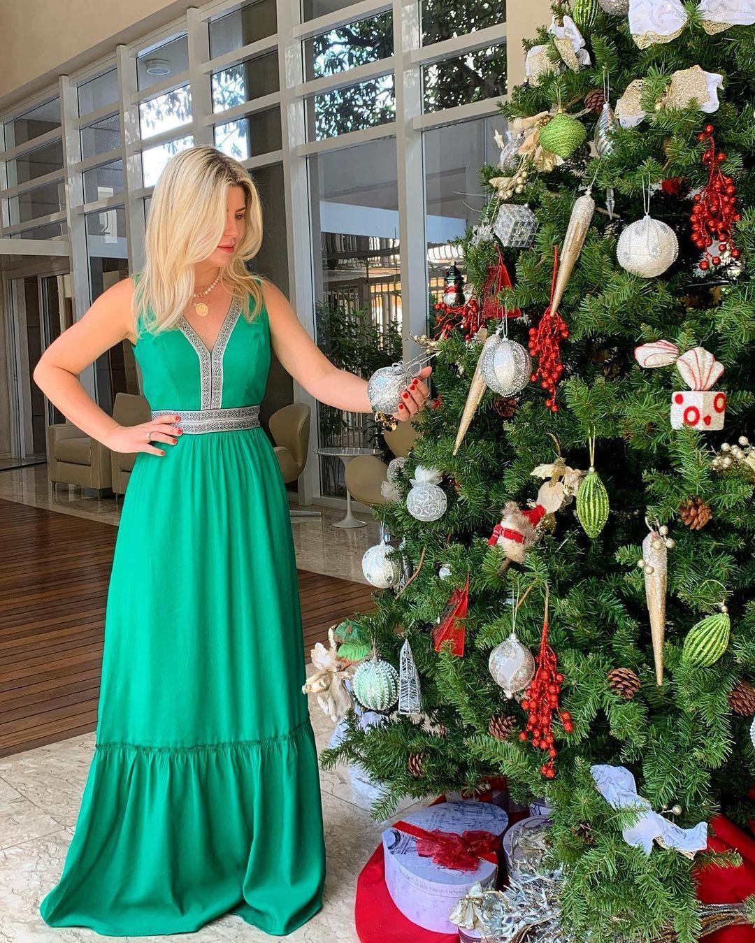 Imagem mostra Íris Stefanelli ao lado de árvore de Natal