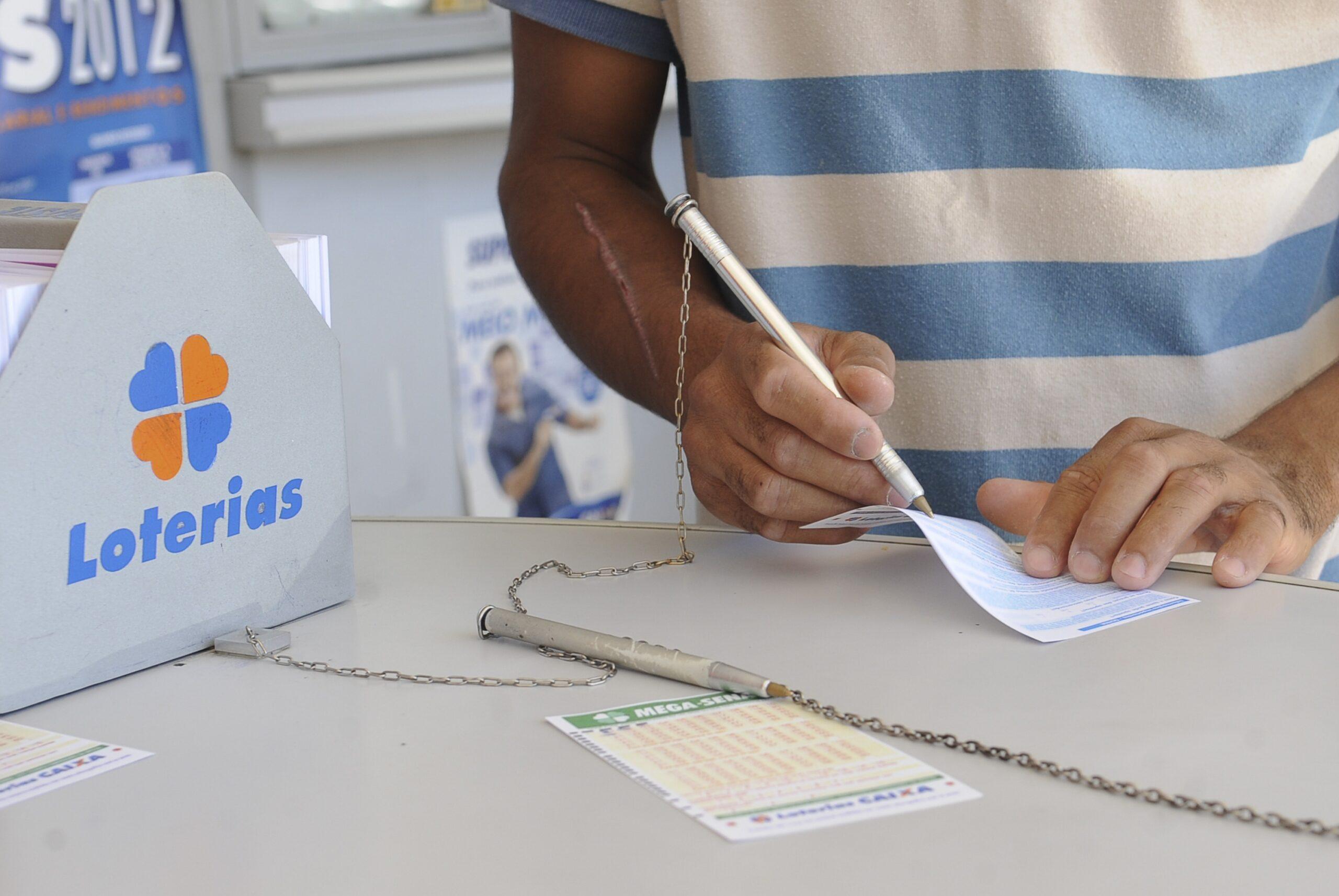 Super Sete 15 - a imagem mostra uma pessoas marcando números em um volante de loteria