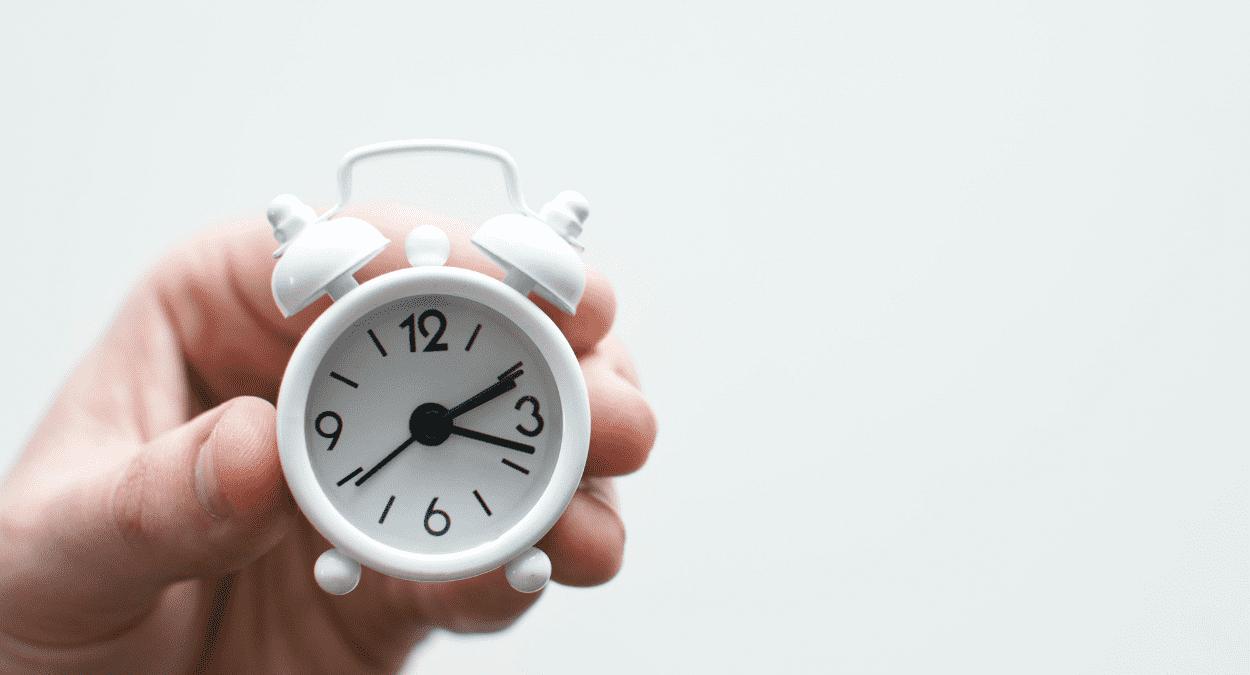 Imagem de uma mão segurando um relógio