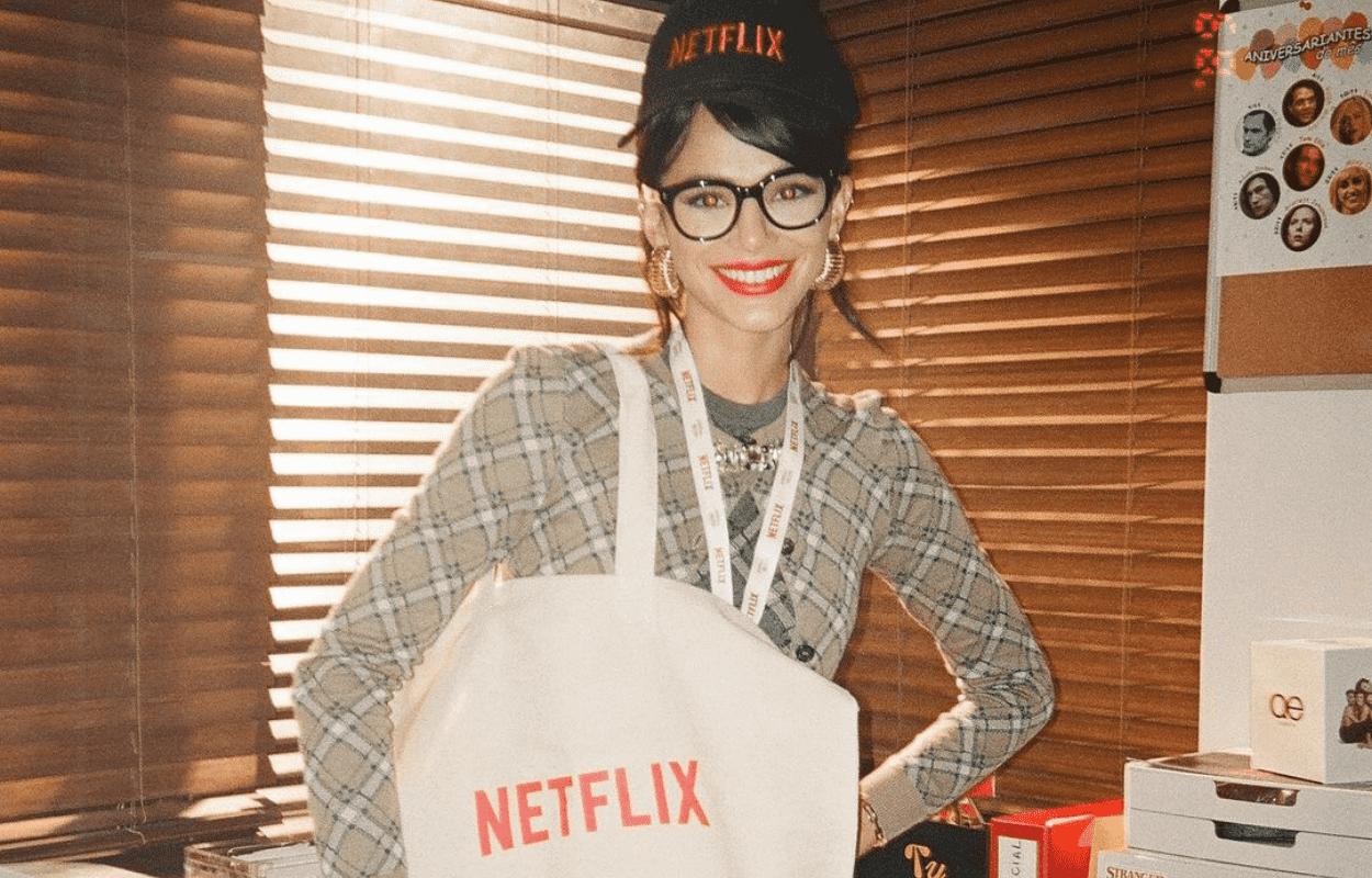 Imagem mostra Bruna Marquezine com boné, bolsa e crachá da Netflix
