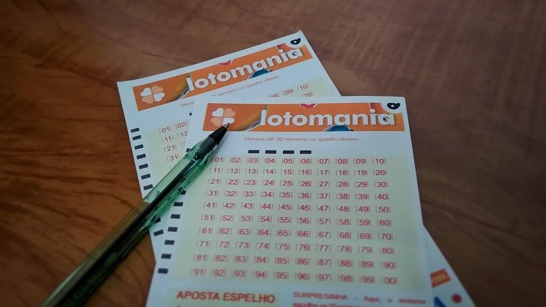A imagem mostra dois volantes da Lotomania e uma caneta