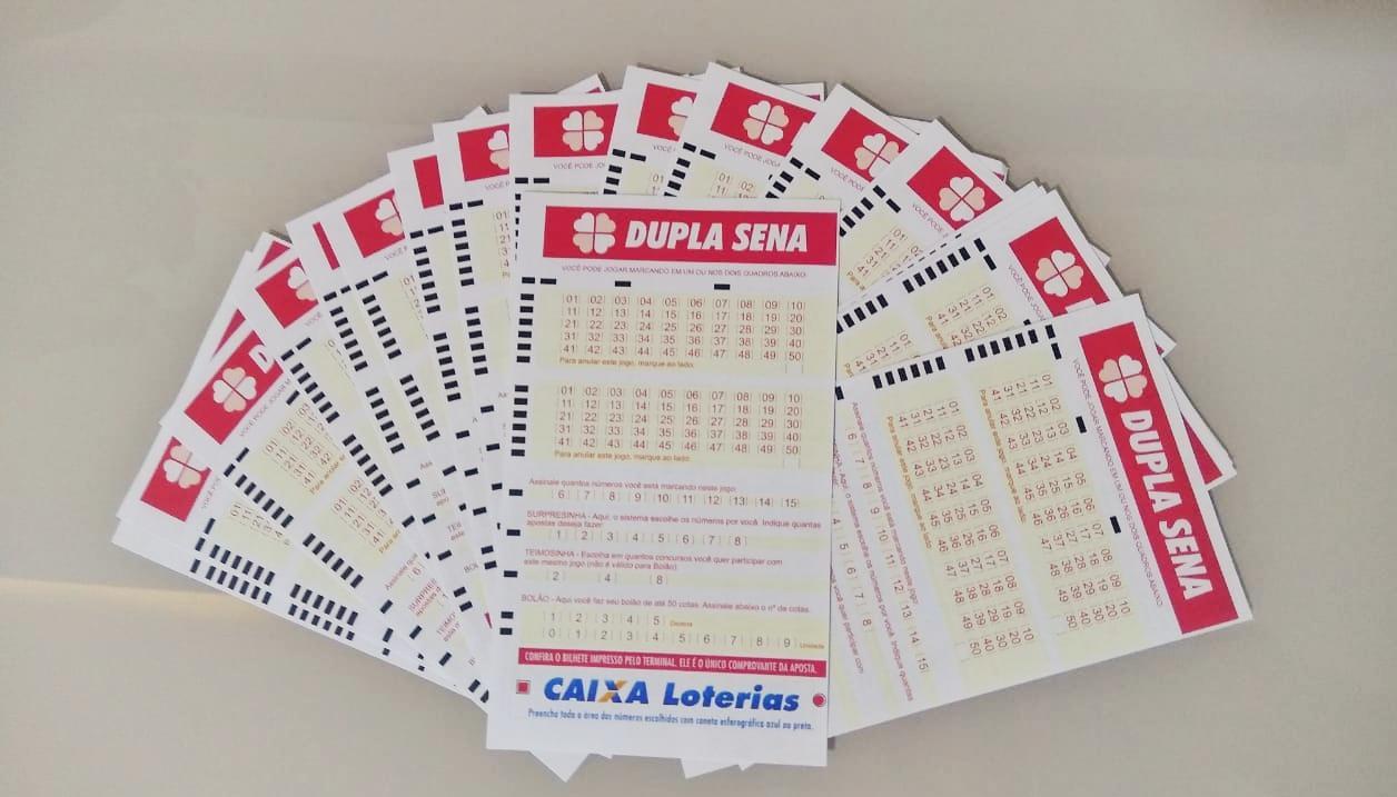 resultado da dupla sena - a imagem contém diversos volantes da dupla sena em branco formando um leque sob uma mesa