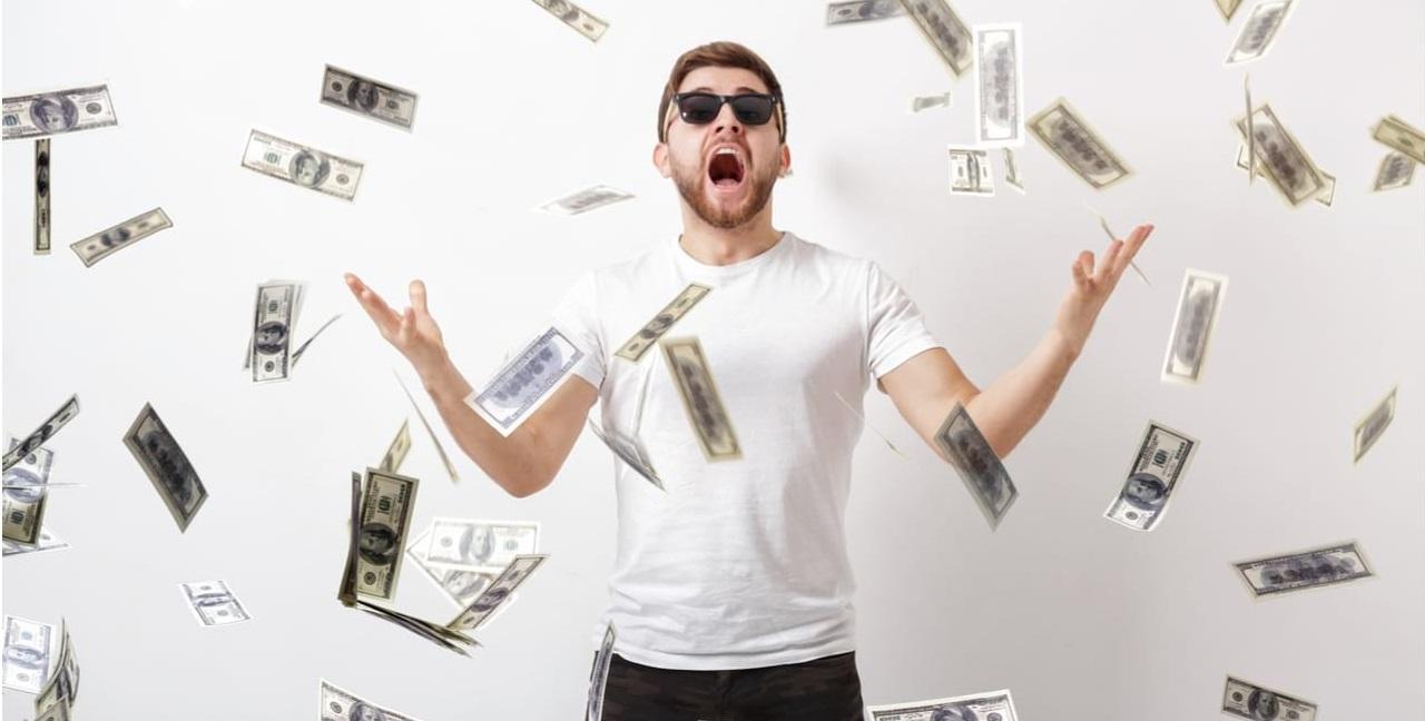 Mega da Virada 2020 - A imagem mostra uma homem comemorando uma chuva de dinheiro